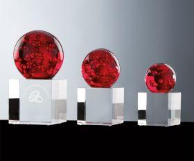 Kristallkugel rot auf Kristallsockel